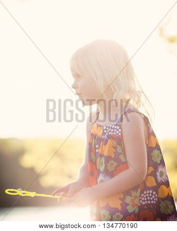 Sunflare. Caucasian girl playing at sunset with bubbles outside