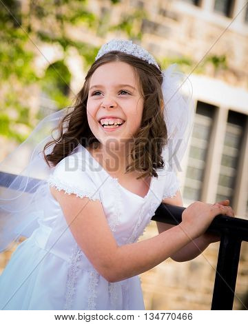 Caucasian girl wearing first holy communion dress. Outdoors.
