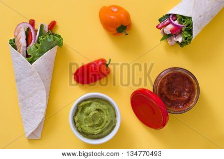 Mexican chicken fajita with peppers lettuce and onion on yellow background