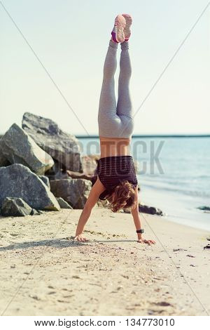Woman Practicing Yoga At The Beach