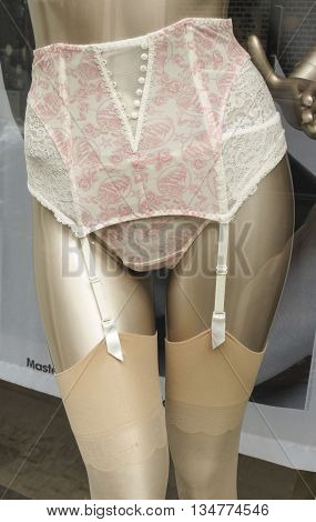 COPENHAGEN DENMARK - CIRCA JUNE 2016: Aubade white and pink suspender belt with four straps and nude stockings worn by a mannequin in a shop window