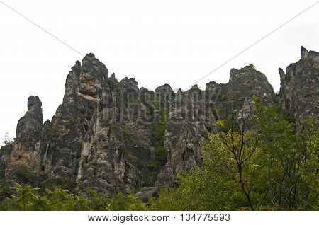 Eroded rocks in mountains against gray cloudy sky background