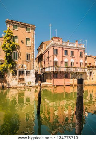 The old Chioggia houses create colorful reflections in the water of the canals.