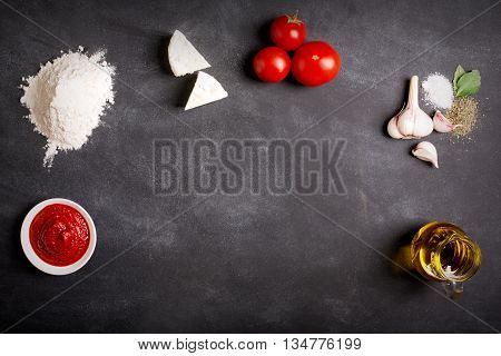 Raw pizza ingredients on the chalkboard with copy space on the center. You can put your image or inscription at the center