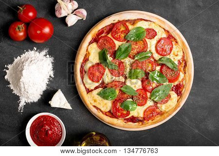 Pizza (margherita) and ingredients on the chalk board (top view)