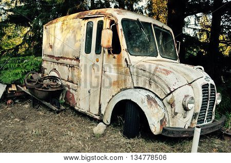 Decaying old milk truck with no wheels.