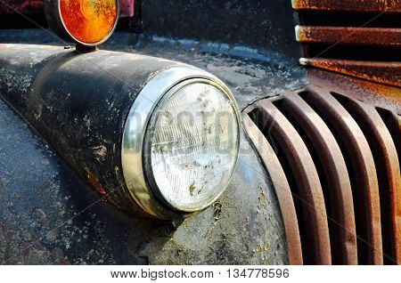 Old headlight on a vintage truck showing its rusted grill.