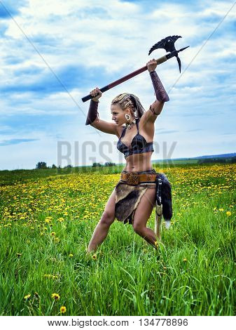 Beautiful athletic woman in the image of an ancient barbarian warrior on summer nature background.