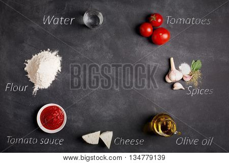 Ingredients of pizza on the chalkboard (vegetables spices mozzarella oil and flour)
