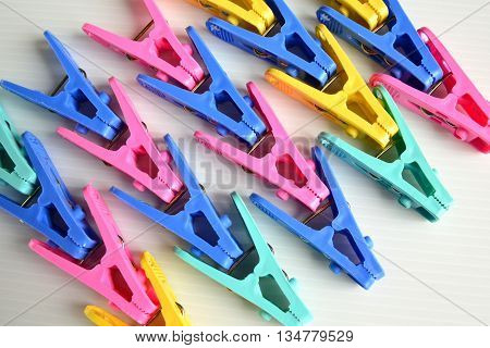 Many Colorful Clothes Pegs on white background