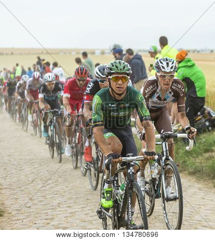 Quievy,France - July 07 2015: Bryan Coquard (Europcar Team) and Romain Bardet (AG2R La Mondiale Team) riding in front of a group of cyclists on a cobblestone road during the stage 4 of Le Tour de France 2015 in Quievy France on 07 July2015.