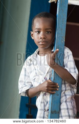 A child standing near an iron pillar and looking at the camera