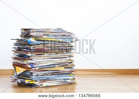 Pile of colorful newspapers and advertisements in front of a light background