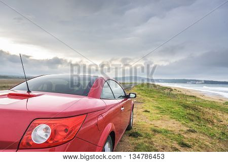 SOZOPOL, BULGARIA - MAY 3: Red car Renault Megane Cabriolet on the wild sand sea beach, on May 3, 2016 in Sozopol, Bulgaria.