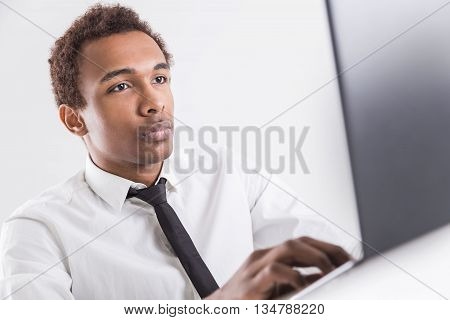 Concentrated african american businessman with tie sitting at office desktop using laptop