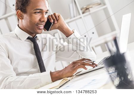 Side view of friendly african american businessman using notepad and laptop on office desktop while having mobile phone conversation. Bookshelf with documents in the background