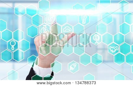 Business concept with businesswoman hand pressing digital honeycomb patterns with business icons