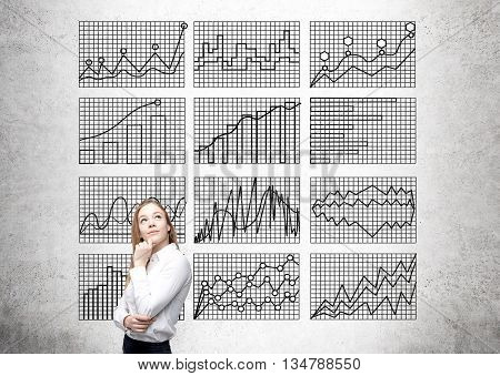Thoughtful young woman standing against concrete wall with business charts on grid