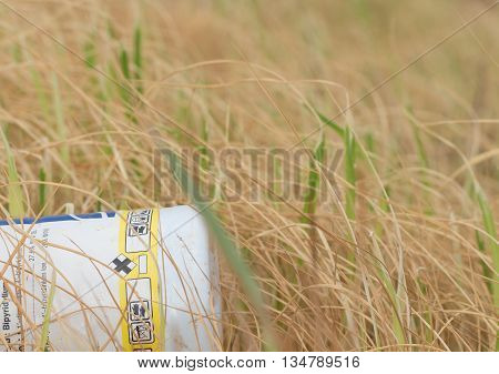 yellow grass damaged by herbicide and part of bottle herbicide