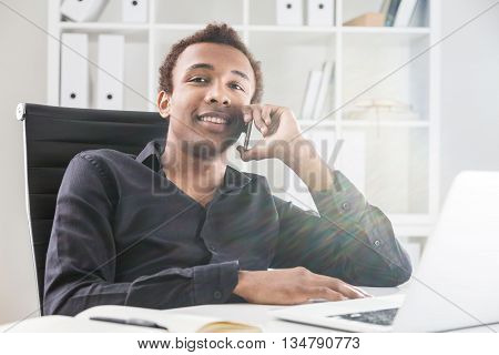 Cheerful african american businessman having phone conversation in office. Bookshelf with documents in the background