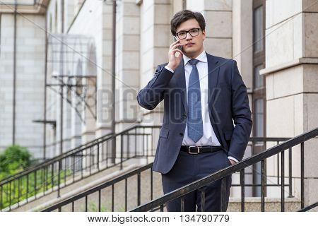 Young attractive businessman in suit having mobile phone conversation with beautiful architecture in the background
