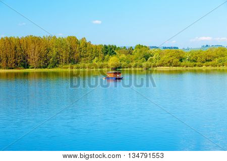 Houseboat on the lake, and trees in the background