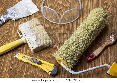 Construction tools: glasses, trowel, roller, knife and brush on wooden background