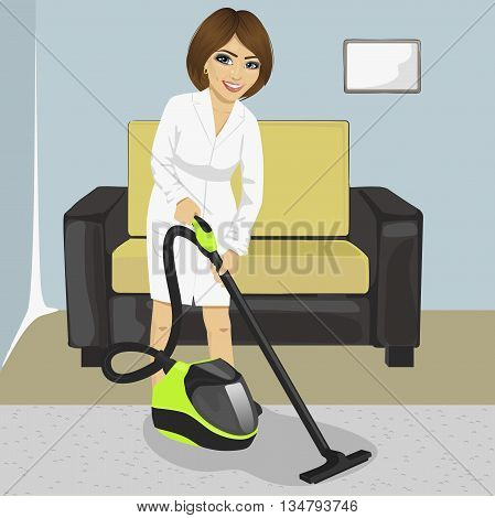 Full length of young woman in white bathrobe cleaning carpet with vacuum cleaner at home