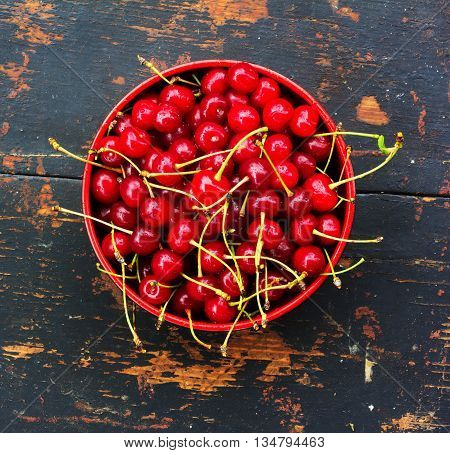 red ripe cherries with tails in a round platet on the old black wood background with crack. close-up top view