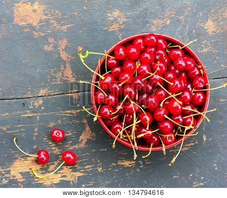 red ripe cherries with tails in a circular plate on an old black wooden background with a crack. close-up view from above