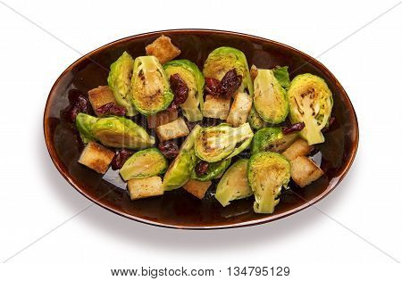 Roasted brussels sprouts with dried tomatoes and croutons isolated on white