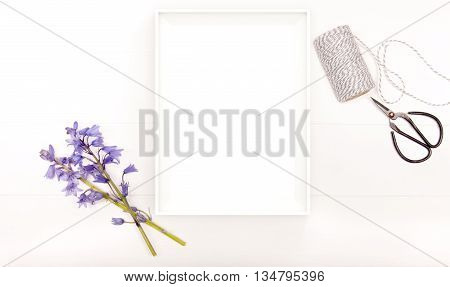 Styled stock photography bluebells on a white wooden floorboard background with scissors and twine. A4 White frame for you to overlay any business promotion instagram message or headline.