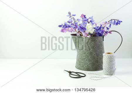 Styled stock floral image bluebells in a little tin jug. Copy space for your business promotion instagram message or headline.