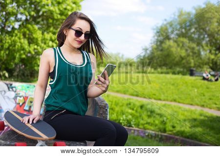 a young skateboarder sitting in the park with her phone
