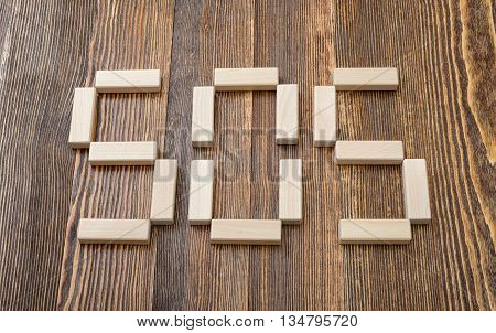 Close-up wooden bricks making form of words SOS. Top view. Concept. Close-up photo. Game of physical and mental skill. Keeping balance. Entertainment activity. Education and development.