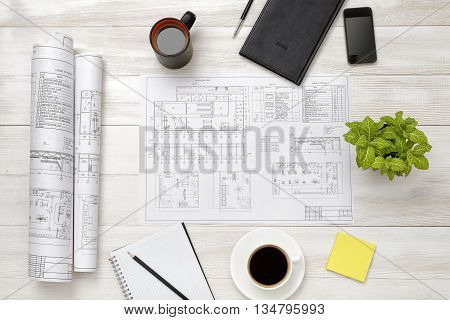 Drawing sketches, magnifier, cup of coffee and houseplant are on wooden surface. Top view compositin. Workplace. Engineering work. Construction and architecture. Architect drawing. Office workplace.