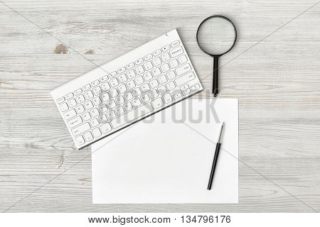 Office workplace with keyboard, pen, white blank paper and magnifier. Top view composition. Willingness to work overtime. Keeping healthy. Contribution to wellbeing. Workplace of office man.