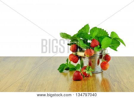 Delicious strawberries in a bucket . Gardening. Hobby. Agriculture. Own harvest. Summer. Vitamins. strawberries with leaves in basket on wooden table / Isolated on white background without shadows /. Hobbies for the soul.