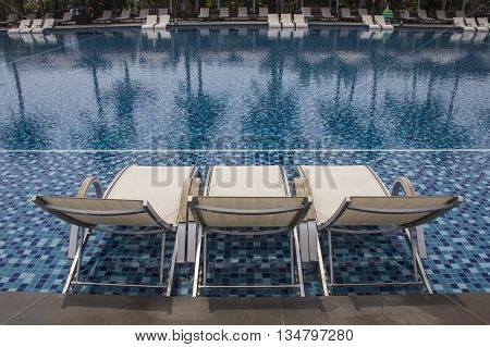 Luxury swimming pool and blue water at the resort with Beautiful luxury pool Chair on its sides and reflections of palm trees
