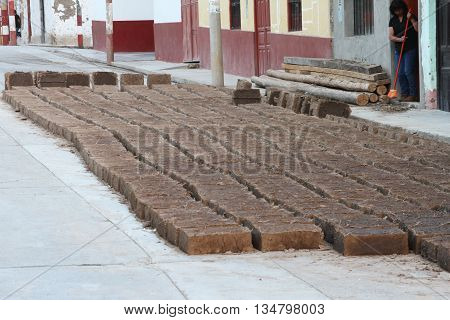 Magdalena Cajamarca Peru - June 16 2016: Woman sweeps sidewalk as adobe bricks dry in the sun in Magdalena Cajamarca Peru on June 16 2016