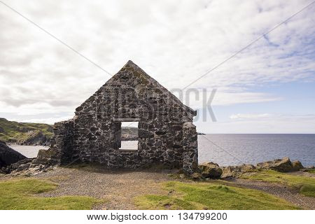 The wall of a ruined stone building provides a frame for the rugged coastline of the Moray Firth