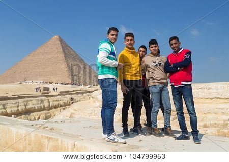 CAIRO, EGYPT - FEBRUARY 1, 2016: Group of local boys posing in front of the Great pyramid of Giza.