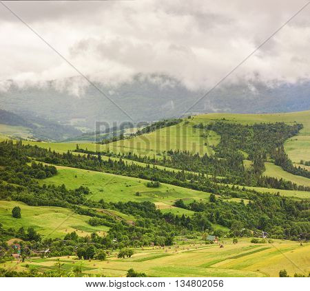 Mountain village on green hill under heavy rainy clouds