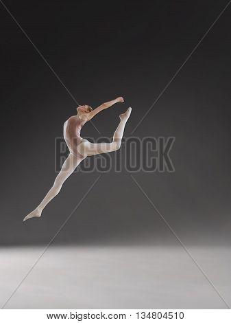 Young beautiful ballerina posing in jump in studio