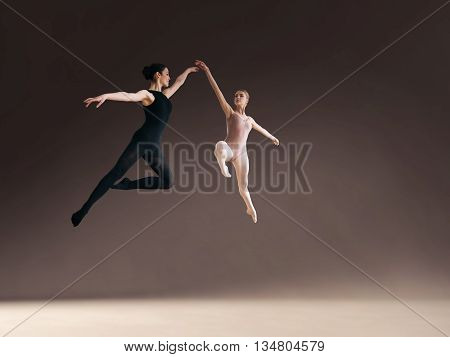Two ballet dancers jumping high in air on gray blackground