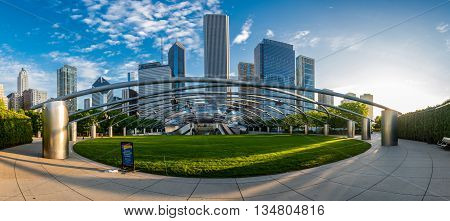 Chicago Illinois: May 27 2016. Jay Pritzker Pavilion Panorama in Millenium Park with downtown Chicago looming behind it