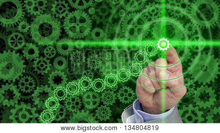 Different sized an shaped green cogs and gears background with a hand pressing a glowing green gear in a chain