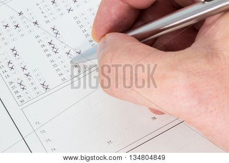 Hand with a ballpen filling out an exam answer sheet