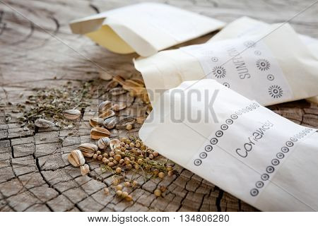 Seed packets and seeds. Focus on coriander and sunflower seeds dill seeds farther back.