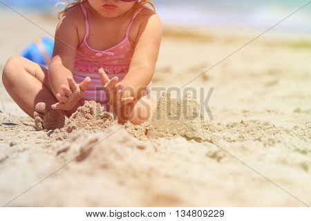 hands of little girl play with sand on tropical beach